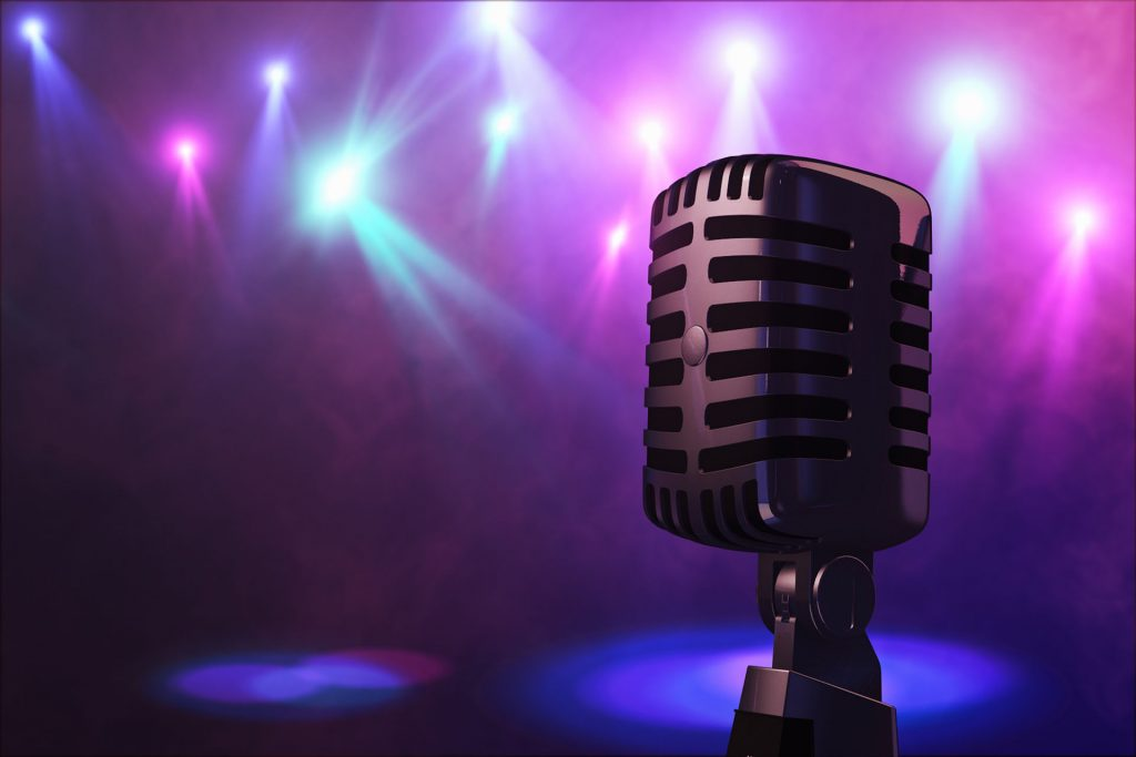 Retro style microphone on stage in the spotlight performance of the musical group. Microphone for rock rock'n'roll and rockabilly music. Microphone in blue light og stage. Music is in the air